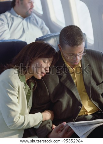 Mature couple relaxing on airplane - stock photo