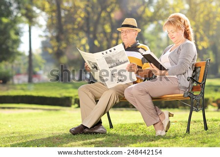 Mature couple relaxing seated on a bench in park  - stock photo