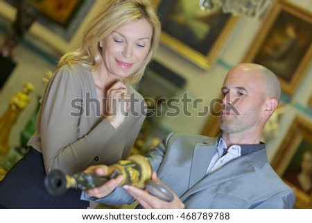 mature couple reviewing item at auction place