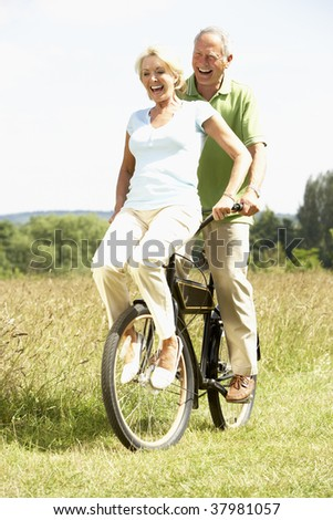 Mature couple riding bike in countryside