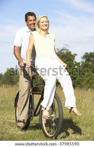 Mature couple riding bike in countryside - stock photo
