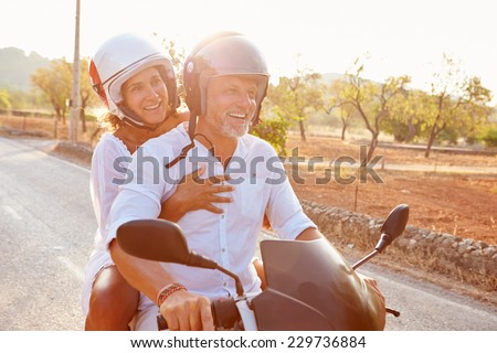 Mature Couple Riding Motor Scooter Along Country Road - stock photo