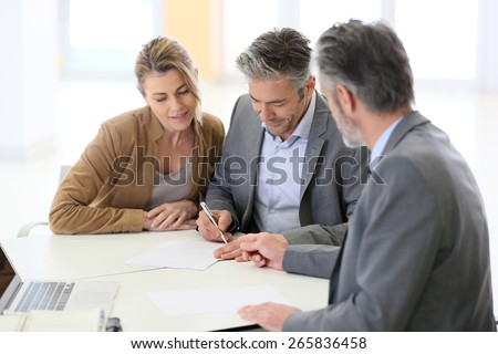 Mature couple signing financial contract at the bank - stock photo