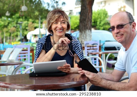 Mature couple sitting and resting in the sidewalk cafe   using a smart phone and digital tablet.. - stock photo