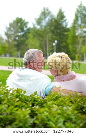 Mature couple sitting and talking in park in summer