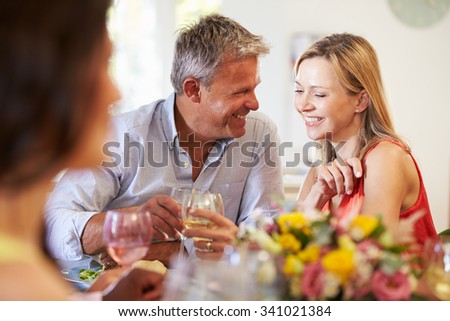 Mature Couple Sitting Around Table At Dinner Party - stock photo