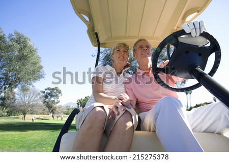 Mature couple sitting in golf buggy on golf course, man driving, smiling, front view, low angle view - stock photo