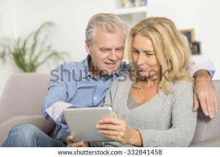 Mature couple sitting in sofa and using tablet pc - stock photo