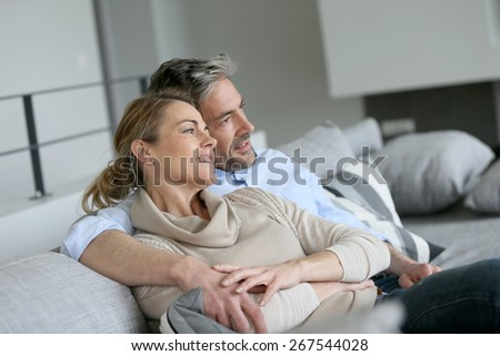 Mature couple sitting in sofa, looking away - stock photo
