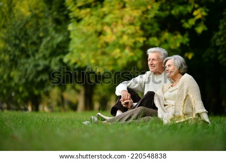 Mature couple sitting on green grass in summer park - stock photo