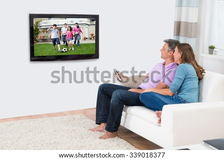 Mature Couple Sitting On Sofa And Enjoying Watching Television