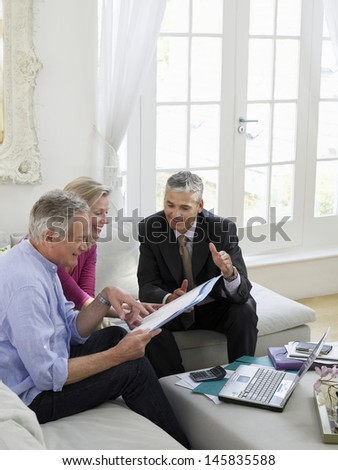 Mature couple sitting on sofa with financial advisor - stock photo