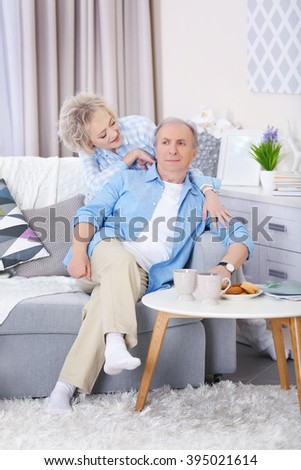 Mature couple sitting together  on a sofa at home