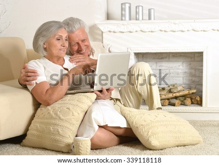 Mature couple sitting with laptop in hotel