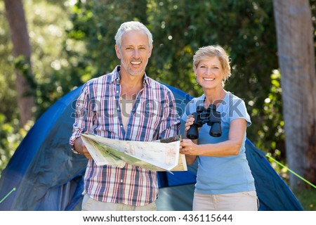 Mature couple smiling and holding binoculars and map on their camp site - stock photo