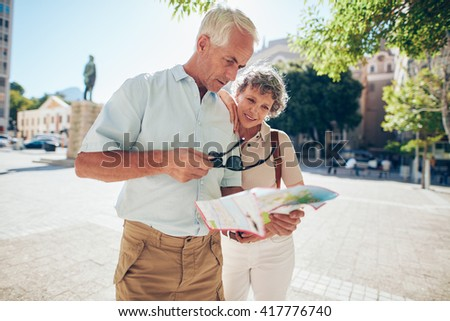 Mature couple standing outdoors in the city looking at a map. Senior man with his wife using city map for finding their location. - stock photo