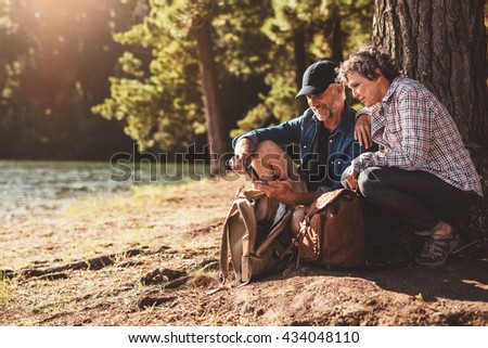 Mature couple stops to check their position by using a compass while out on hike in the forest. Man and woman sitting by a tree in forest using a compass for navigation. - stock photo