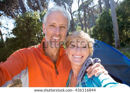 Mature couple taking a photo their camp site - stock photo