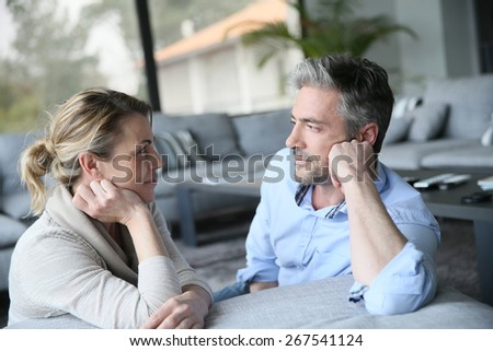 Mature couple talking to each other in sofa - stock photo