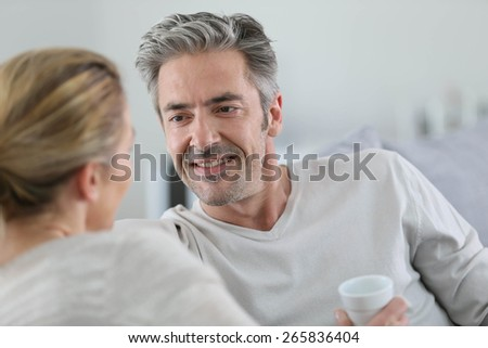 Mature couple talking together in sofa - stock photo