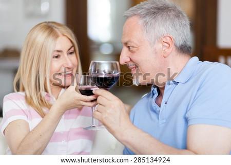 Mature couple toasting wine glasses - stock photo