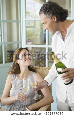 Mature couple toasting with champagne at home.