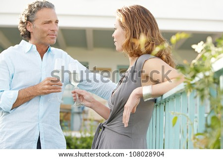 Mature couple toasting with champagne while in a home garden's balcony.