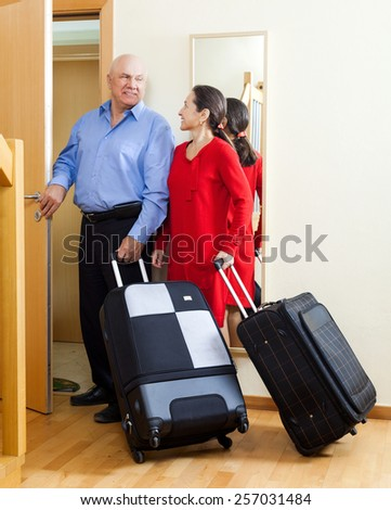 mature  couple together with suitcases leaving the home