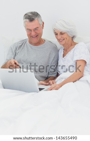 Mature couple using a laptop together in bed - stock photo