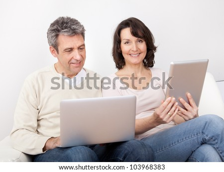 Mature couple using laptop and tablet in couch at home
