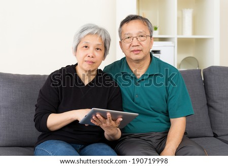Mature couple using tablet computer - stock photo