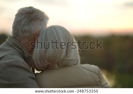 Mature couple walking in the autumn park - stock photo