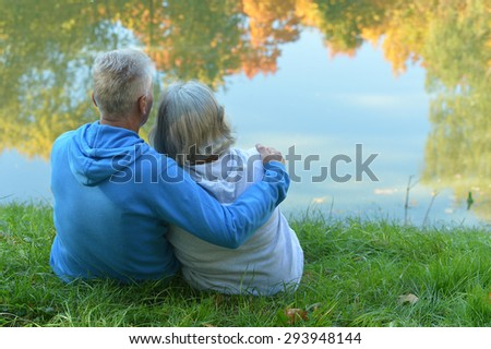 Mature couple walking in the park in the afternoon - stock photo