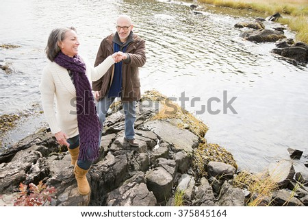 Mature couple walking over rocks - stock photo