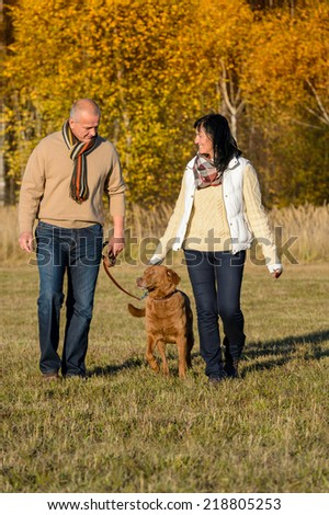 Mature couple walking retriever dog enjoying autumn sunny park