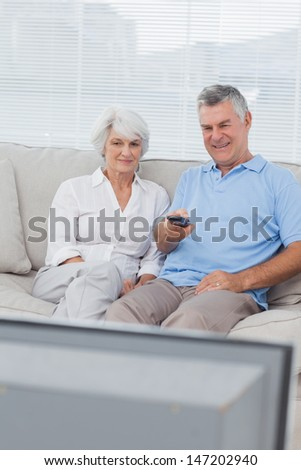 Mature couple watching television on the couch - stock photo
