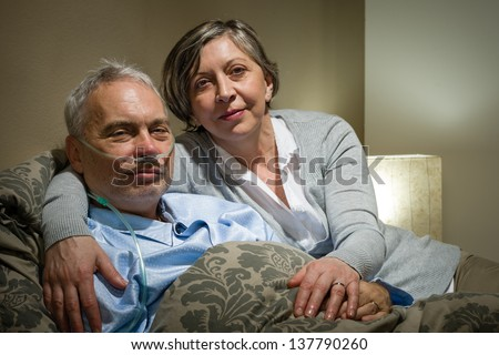 Mature couple wife supporting ill husband at home - stock photo