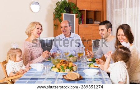 Mature couple with adult kids and grandchildren having meal together - stock photo