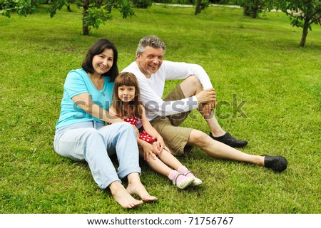 Mature couple with daughter on grass outdoors - stock photo
