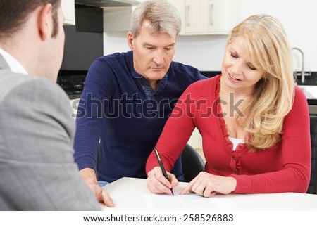 Mature Couple With Financial Adviser Signing Document At Home