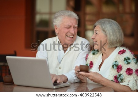 Mature couple with laptop - stock photo