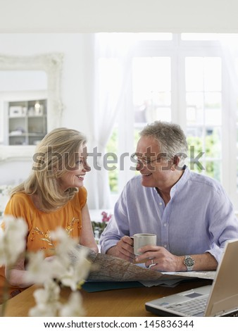 Mature couple with map and laptop sitting at dining table in home - stock photo