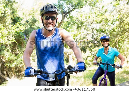 Mature couple with sunglasses riding bike on park