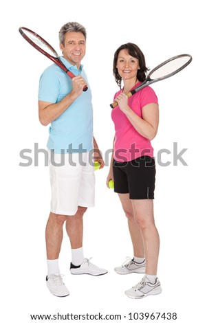 Mature couple with tennis racquets. Isolated on white - stock photo