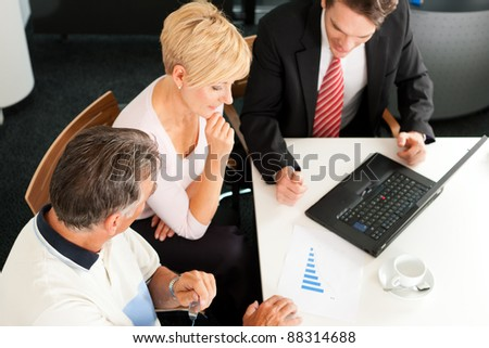 Mature couple with young financial consultant - they are planning their retirement - stock photo