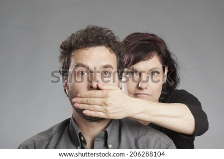 Mature couple woman covering man's mouth