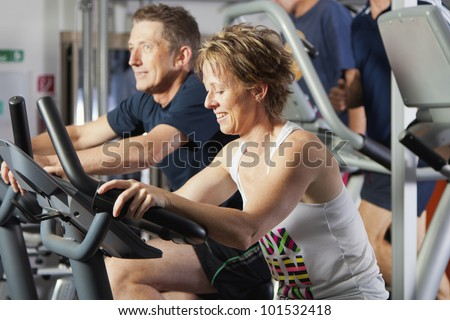 Mature couple working out at fitness center on exercise bikes - stock photo