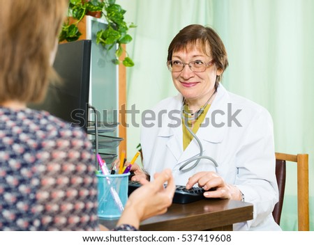 mature  doctor assist patient  in a doctor's office
