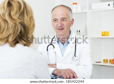 Mature doctor carefully listening his female patient. - stock photo