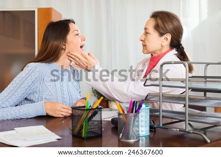 mature doctor doing checkuo young girl in clinic - stock photo